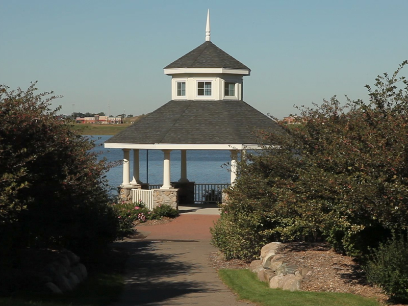Park gazebo and lake with bushes in foreground