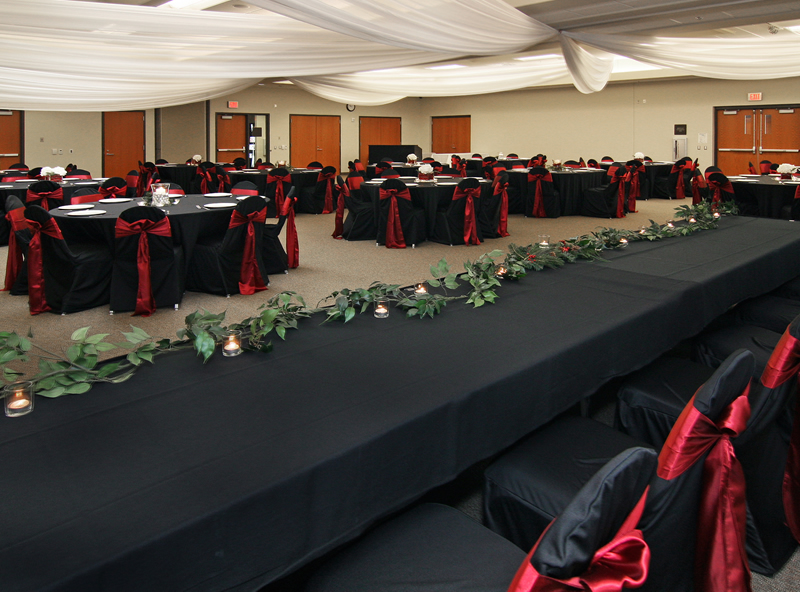 Room set up for banquet with tables, chairs, linens, place settings, head table, and draperies